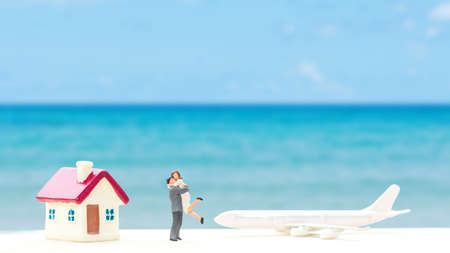 selective focus of miniature tourist couple with plastic toy airplane and home model over blurred blue sea background.