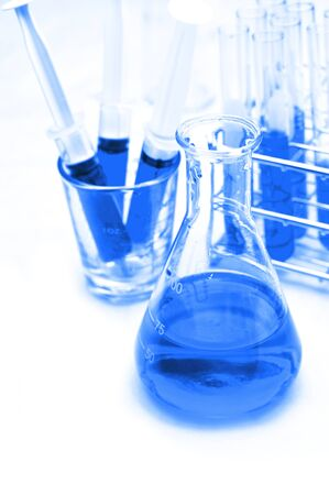 Chemical flask with a blue laboratory test tubes inside photo