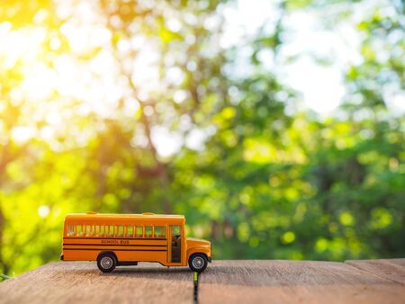 conjunction: yellow school bus plastic and metal toy model on the natural background and sunrise