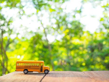 yellow school bus plastic and metal toy model on the natural background and sunrise