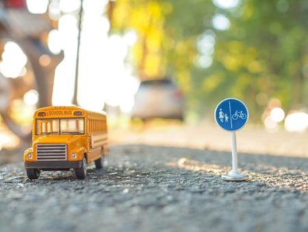Giallo scuolabus di plastica e il modello del giocattolo del metallo sulla strada di campagna Archivio Fotografico - 70335891