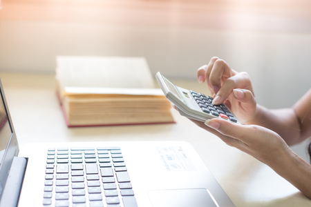 Woman hand is holding a calculator. Computer Key to Calculate Spending Planning Stock Photo