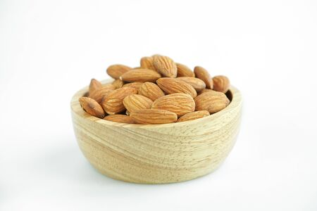 Almond seeds Legumes that are beneficial to the body on a white background in a wooden cup