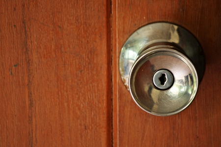Door knob on wooden door photo
