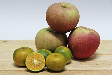 naranja fruta: frutas de color naranja y la manzana roja sobre la mesa de madera
