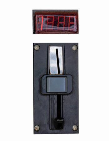 A closeup of a metal coin slot panel from a coin operated machine with entry and exit slots and button on an isolated background photo