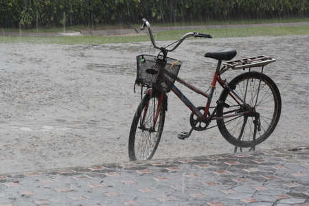 dullness: old bicycle on the street in the pouring rain