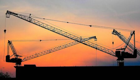 Industrial construction cranes and building silhouettes over sun at sunrise   photo