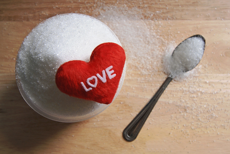 text love on sugar in a cup on wood table background photo