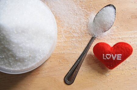 text love with sugar in a cup on wood table background photo
