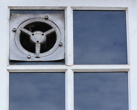old electric air fan or the ventilator on a window  photo