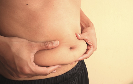 morbidity: Man is holding his too fat tummy Stock Photo