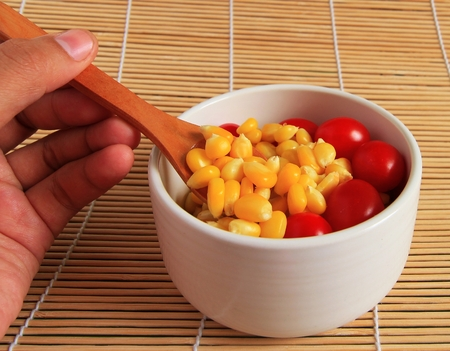 husk tomato: Ripe corn and tomatoes in bowl on a plate on the table