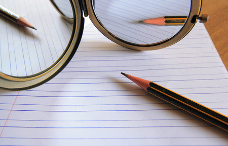 mirror image: pencil lying on a blank paper with a mirror image, Creative work, writing, drawing etc.
