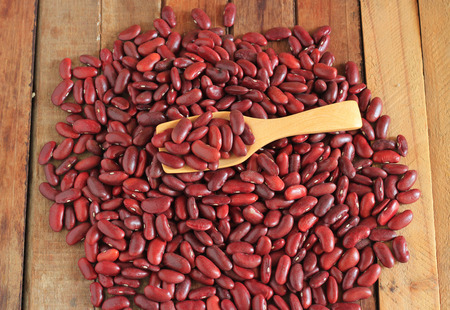 rajma: dried red beans on a wooden spoon and wood background