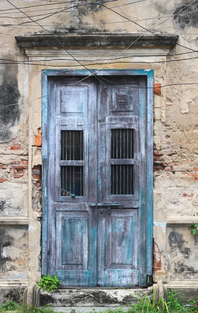 old wooden door: old house white wall with blue door