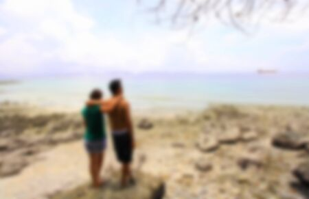 Man and woman standing arm in arm on a rock by the sea,blurred for presentation effect, abstract background Stock Photo