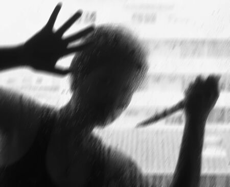 shadowy: Shadowy figure with a knife behind glass,soft focus