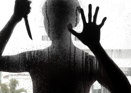 Shadowy figure with a knife behind glass,soft focus