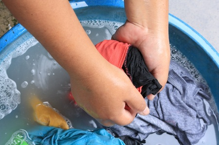 major household appliance: washing clothes by hand in plastic tubs