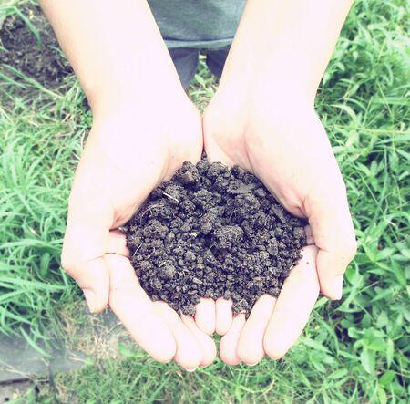 earth handful: Vintage Style,Female hands full of soil over soil background, Representing fertility