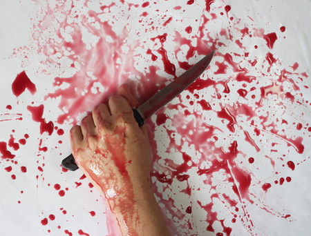 Conceptual image of a victim hand holding a sharp knife with blood on it resting on a concrete floor. Concept photo of murder and crime