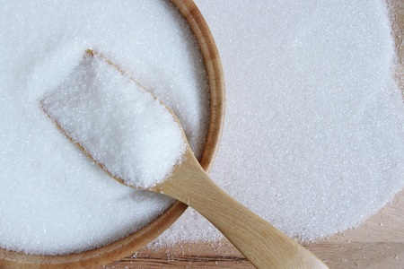 white sugar in wood spoon
