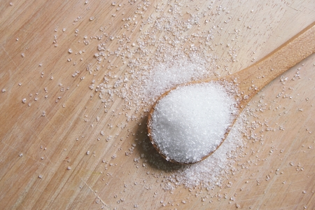 cuchara: azúcar blanco en la cuchara de madera en la mesa de madera