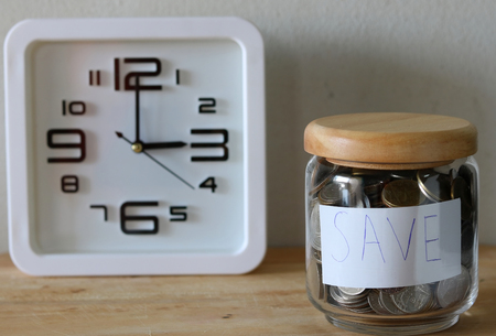 behind scenes: save money for investment concept money in the glass , a clock is behind the scenes