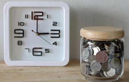 behind the scenes: save money for investment concept money in the glass , a clock is behind the scenes