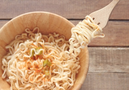 the instant noodles: Instant noodles on fork with wood bowl background