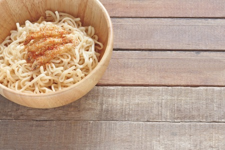 pescado frito: wood bowl of noodles with fried fish on wooden table