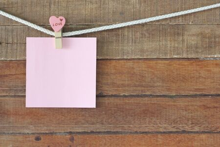 peg board: love note paper on wooden background