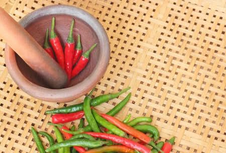basket weaving: chili in mortar on wooden textured basket weaving background Stock Photo