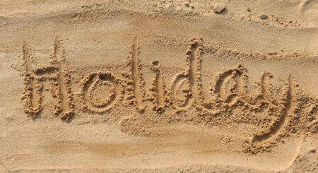 sand writing: Holiday - sand writing on the beach