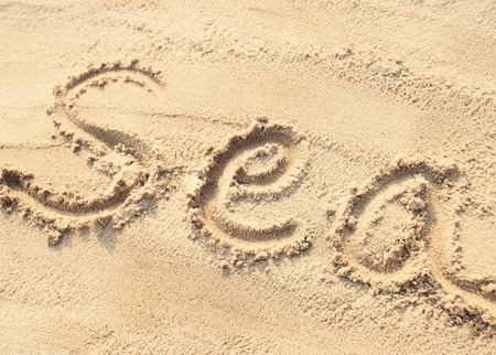 sand writing: Sea - sand writing on the beach, vintage style Stock Photo
