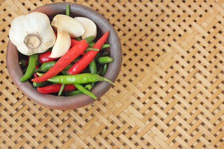 basket weaving: chili and garlic in mortar on wooden textured basket weaving background Stock Photo