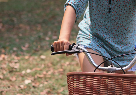 young adult woman: Woman riding bicycle with her hand Stock Photo