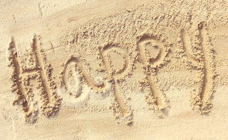 sand writing: Happy - sand writing on the beach