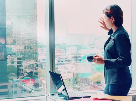 Zijaanzicht van Business vrouw kijkt uit het raam met een kopje koffie in de hand Stockfoto
