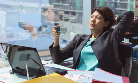 phon: Business woman in the office with views of window and coffee cup her hand