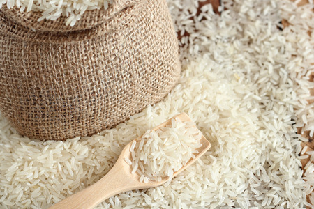uncooked: White uncooked rice on wood spoon