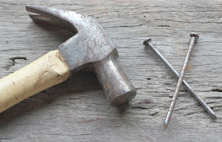 pounding head: Hammer and nails on wood background
