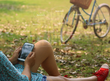 passive income: woman using mobile smart phone at the park , touch screen passive income , Business, technology, internet and networking concept