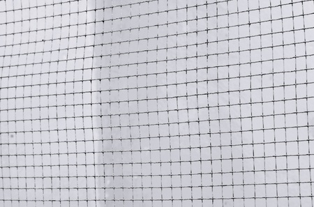 prison system: Structure of mesh metal fence on Dark cement wall background, black and white tone Stock Photo