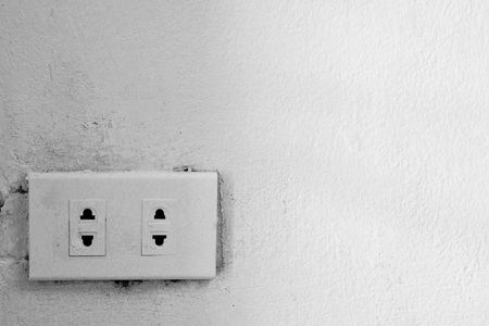 grounded plug: old electrical outlet on a wall Stock Photo