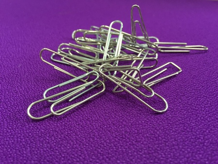 Image of silver paper clip isolated on purple background