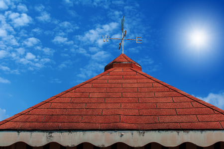 blowing of the wind: Rooster weather vane on roof and blue sky background