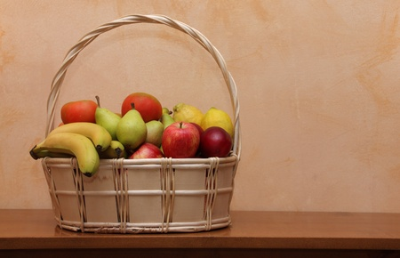 Basket of wicker with fruits and vegetables on table of wood