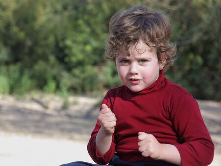 waistcoat: Blond boy with curly hair wearing a red vest in the field Stock Photo
